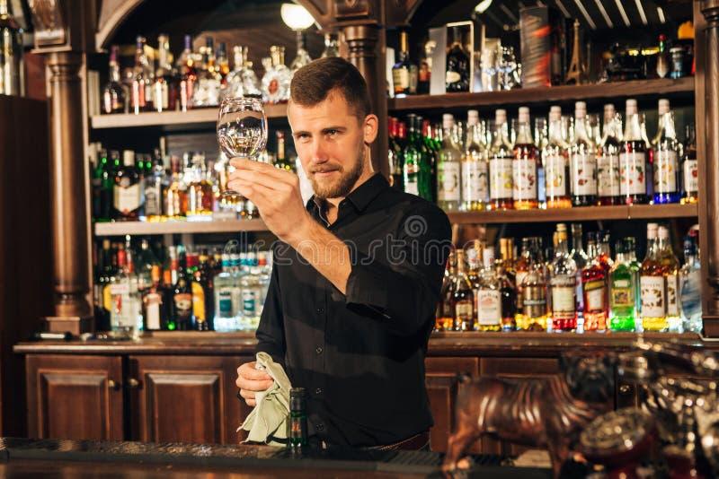侍酒者抹一块玻璃 免版税库存图片