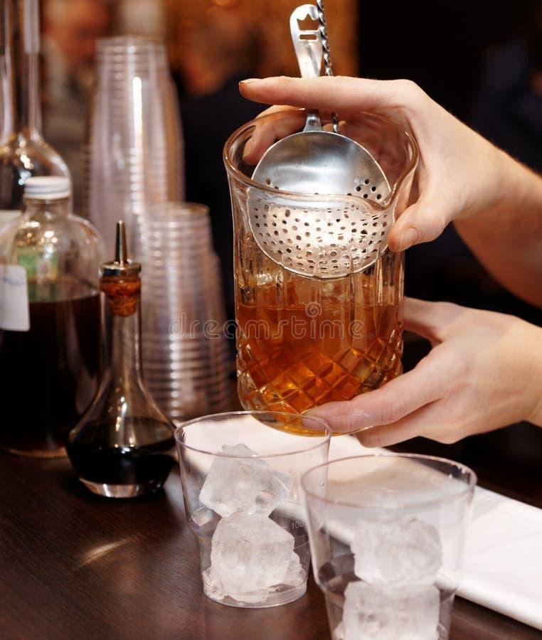 侍酒者是费劲的鸡尾酒入玻璃 库存图片
