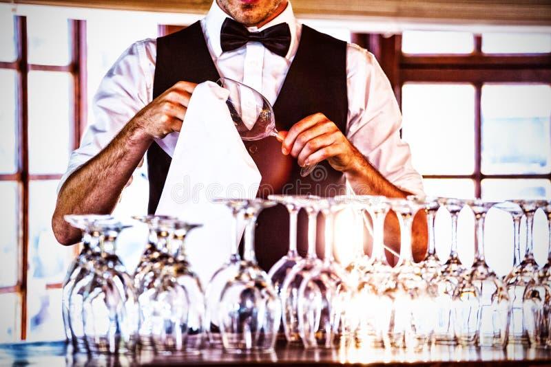 侍酒者清洁葡萄酒杯的中间部分 免版税库存照片