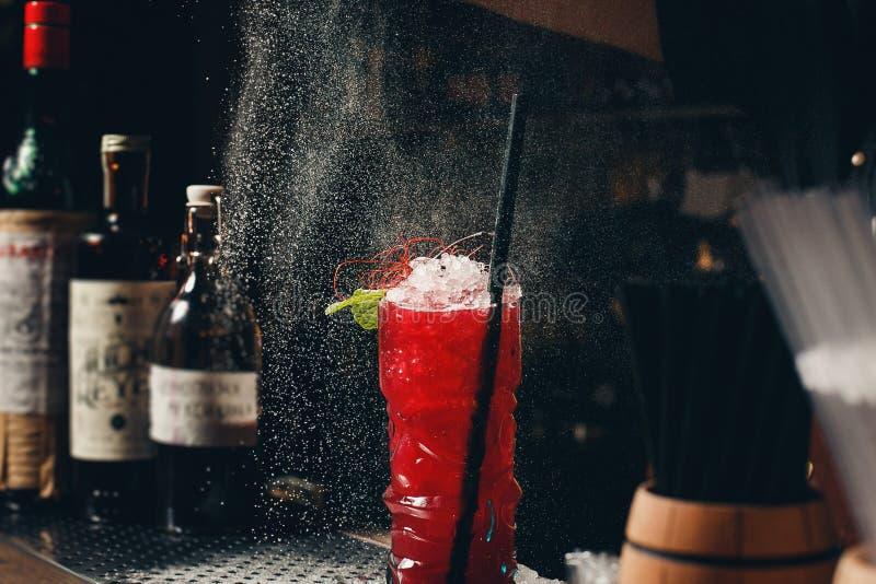 侍酒者` s递洒汁液入鸡尾酒杯充满在黑暗的背景的酒精饮料 免版税库存图片