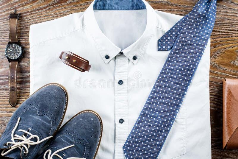 供以人员与正式衬衣、领带、鞋子和辅助部件的` s经典衣裳成套装备平的位置 库存照片