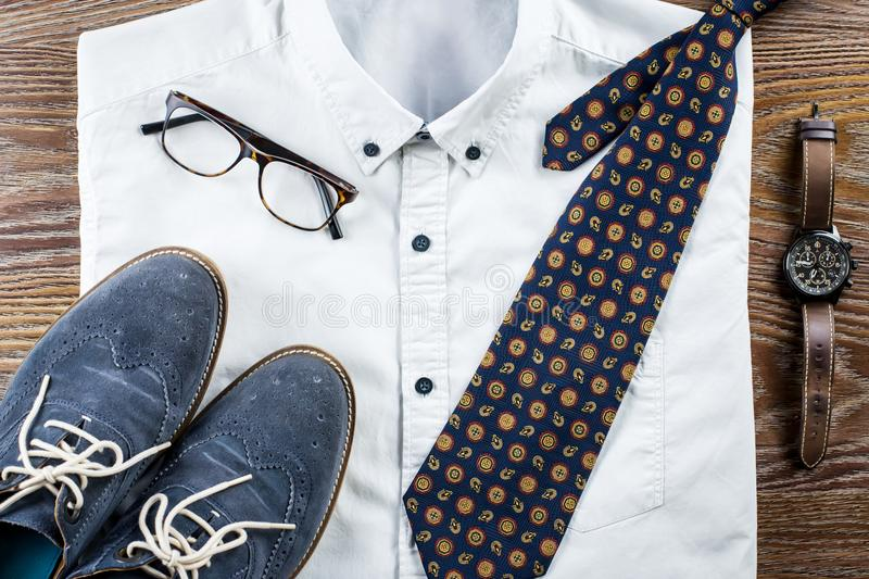 供以人员与正式衬衣、领带、鞋子和辅助部件的` s经典衣裳成套装备平的位置 免版税库存照片