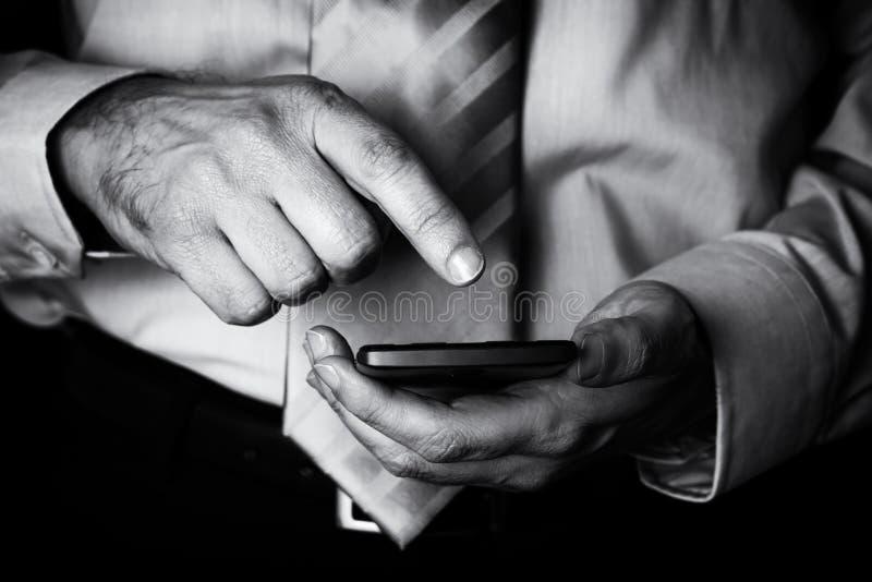 供以人员举行的和触摸屏或显示与一个手机、手机或者智能手机的手指 免版税库存照片