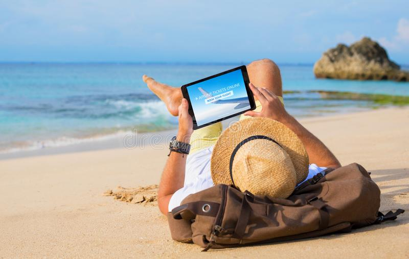 供以人员买的飞机票在网上在片剂,当放松在海滩时 免版税库存照片