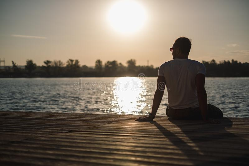 供以人员享受日落,当坐由河时 免版税库存图片