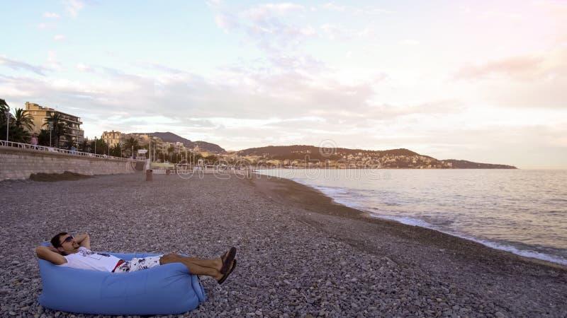 供以人员休息和享受说谎在海岸的空气沙发的地中海看法 免版税库存照片