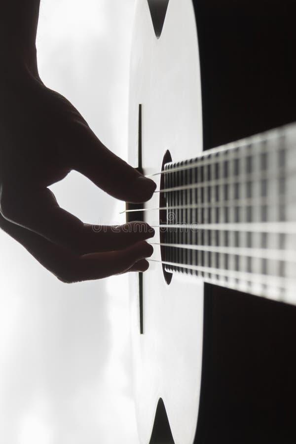 供以人员使用在古典吉他的` s手反对背景  免版税库存图片