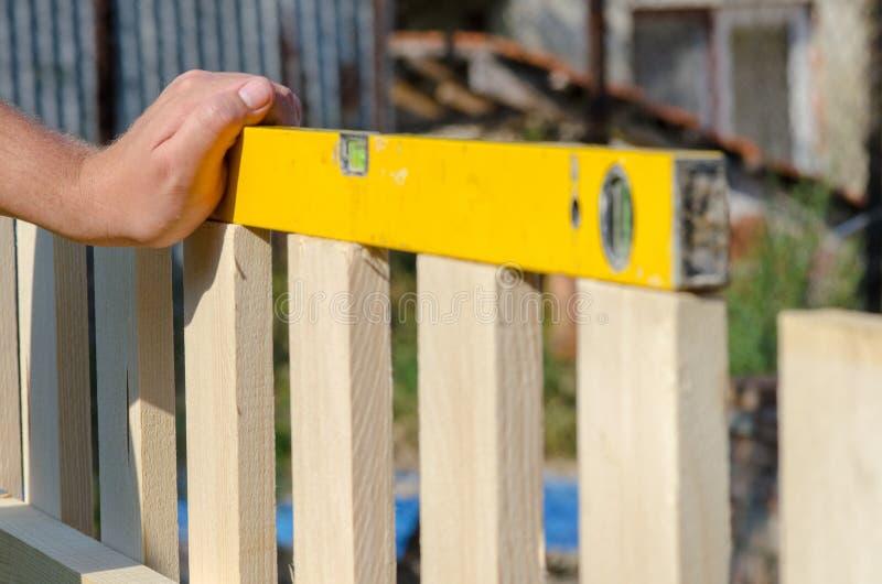 供以人员修造木篱芭和检查与水平仪 关闭他的手和工具在DIY概念 免版税库存照片