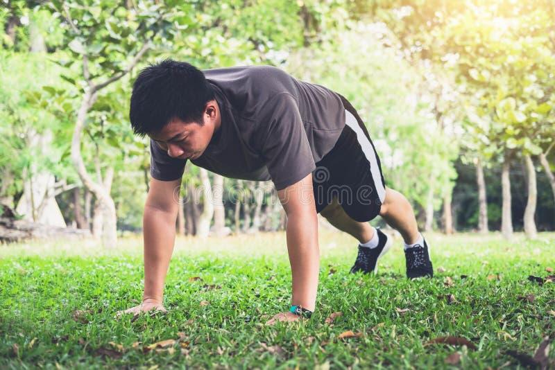 供以人员俯卧撑锻炼做外面在草的锻炼健身  免版税库存照片