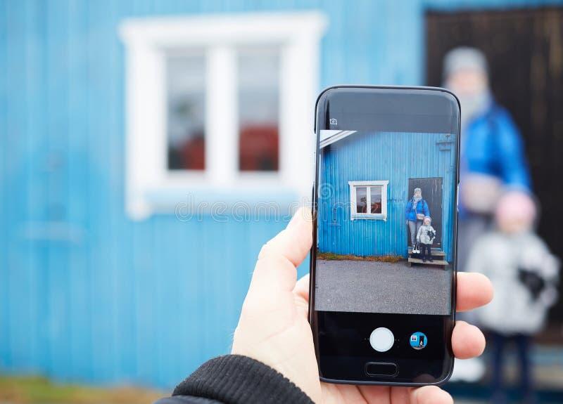 供以人员做照片的手一名女孩和妇女有一个手机的 在一个手机的选择聚焦 库存照片