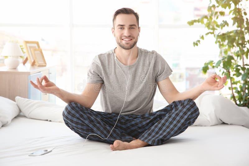 供以人员做瑜伽和听到在床上的音乐 库存照片