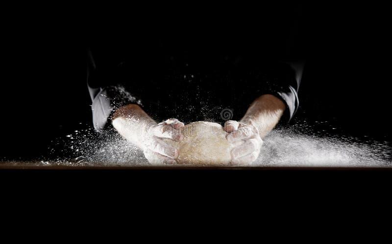 供以人员关上面团入造成面粉的桌飞行 免版税库存照片