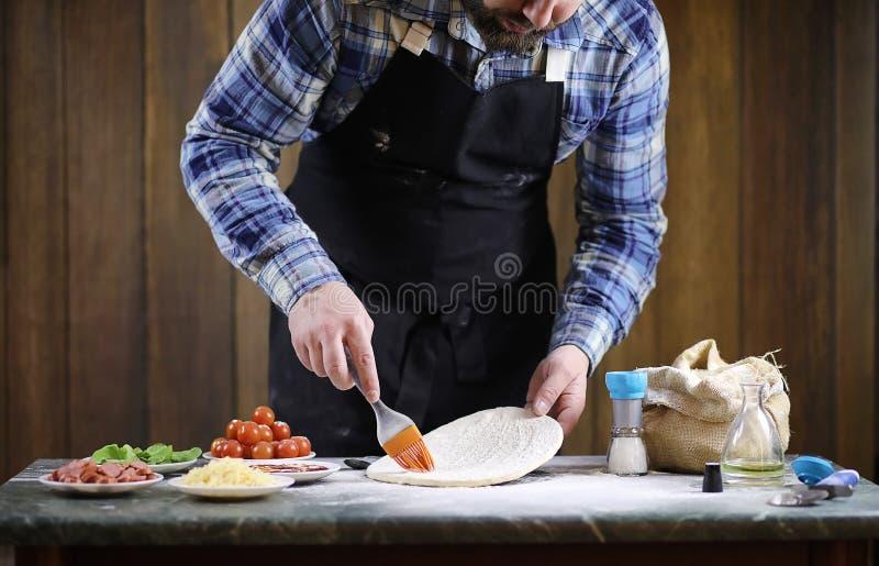 供以人员准备薄饼,揉面团并且投入成份 免版税库存照片