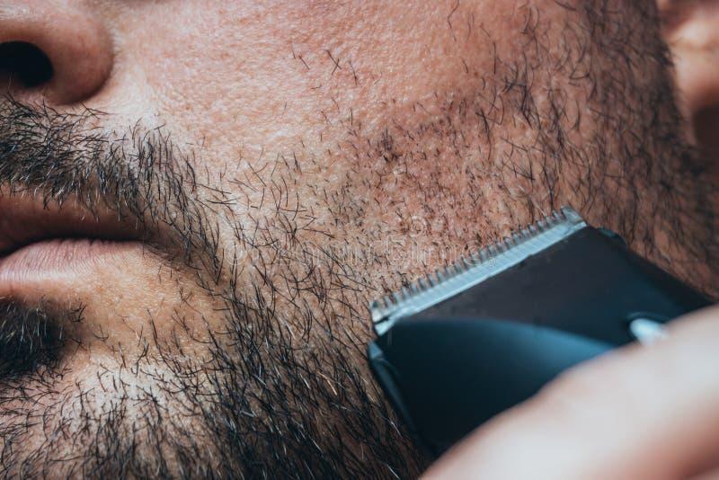 供以人员刮他的与头发剪刀或电整理者的刺毛 胡子关心和理发店 图库摄影