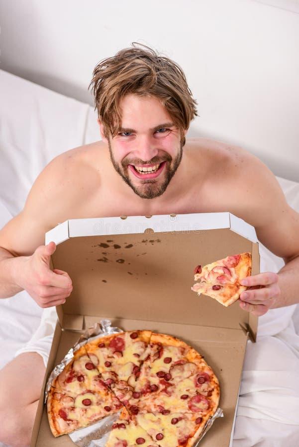 供以人员吃低贱食物早餐的有胡子的英俊的人在床上 人喜欢早餐饥饿的年轻人的比萨  免版税库存照片