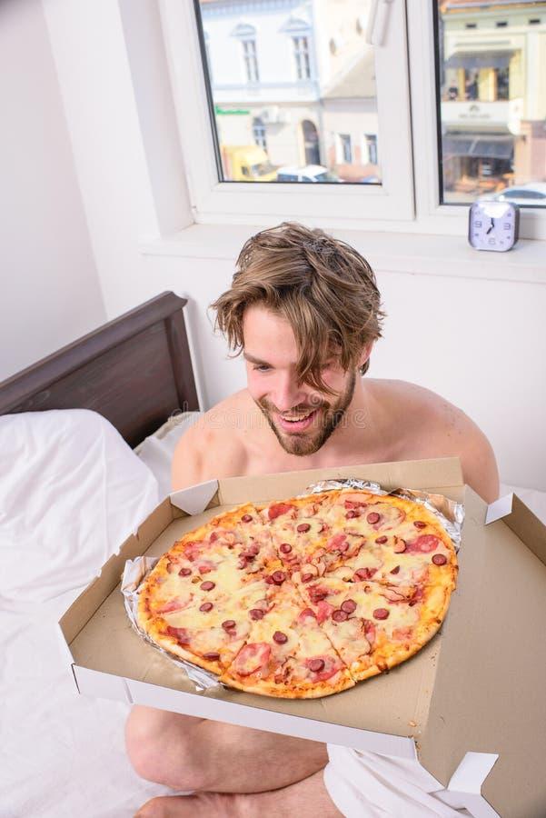 供以人员吃低贱食物早餐的有胡子的英俊的学士在床上 人喜欢早餐断裂饮食概念的薄饼 免版税图库摄影
