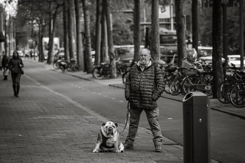 供以人员和他的狗,街道画象,相似的姿势 免版税图库摄影