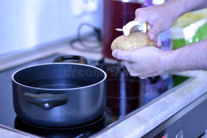 供以人员在一个电火炉特写镜头的削皮土豆 库存图片