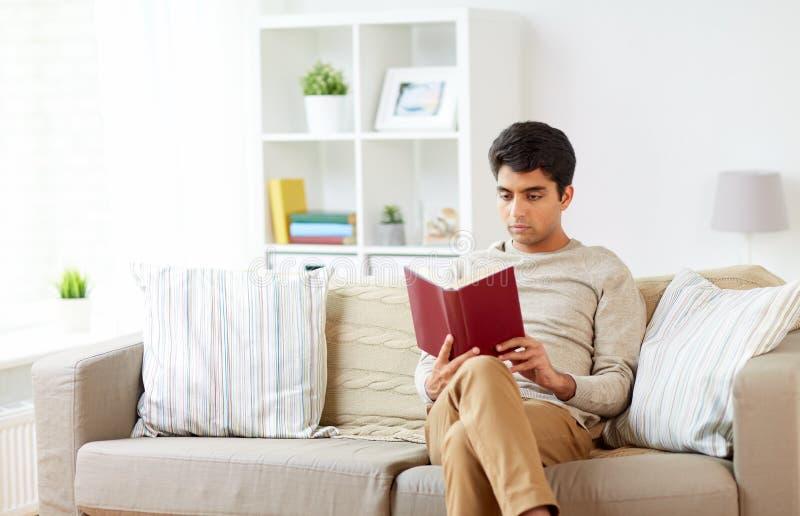 供以人员在家坐沙发和阅读书 免版税库存图片