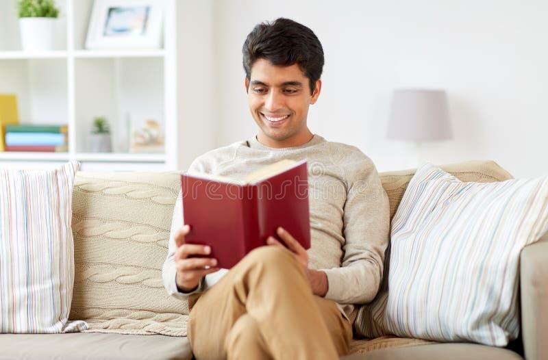 供以人员在家坐沙发和阅读书 库存图片