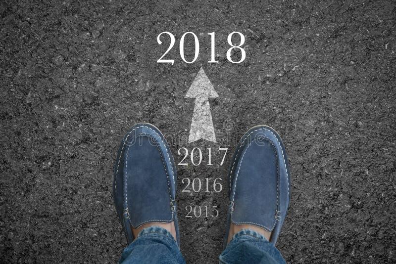 供以人员在柏油路的脚与起动新年2018年 库存图片