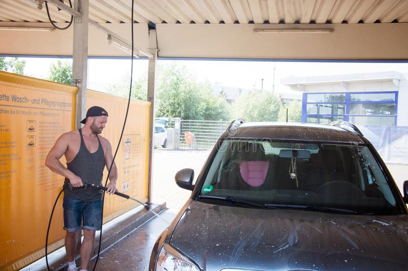 供以人员在洗车的工作者洗涤的汽车` s合金轮子 免版税库存图片