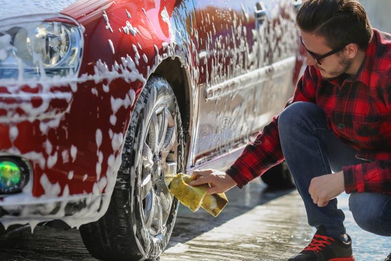 供以人员在洗车的工作者洗涤的汽车` s合金轮子 免版税库存照片
