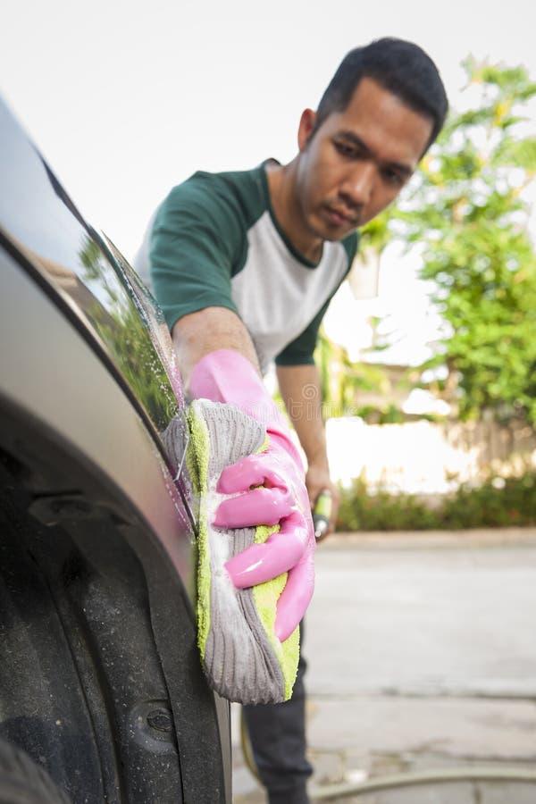 供以人员在洗车的工作者洗涤的汽车` s 清洁概念洗碗盘行为液体海绵 库存图片