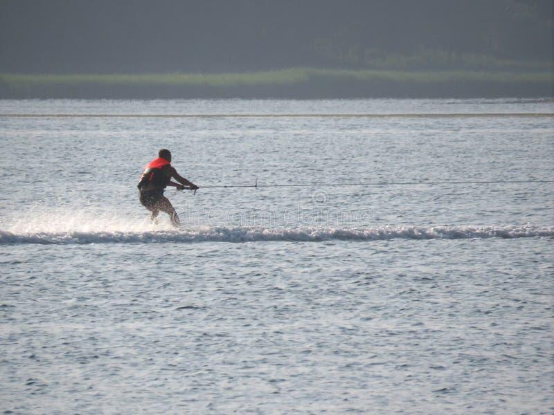 供以人员在海的滑水竞赛在日落靠近绿色海滩 免版税库存图片