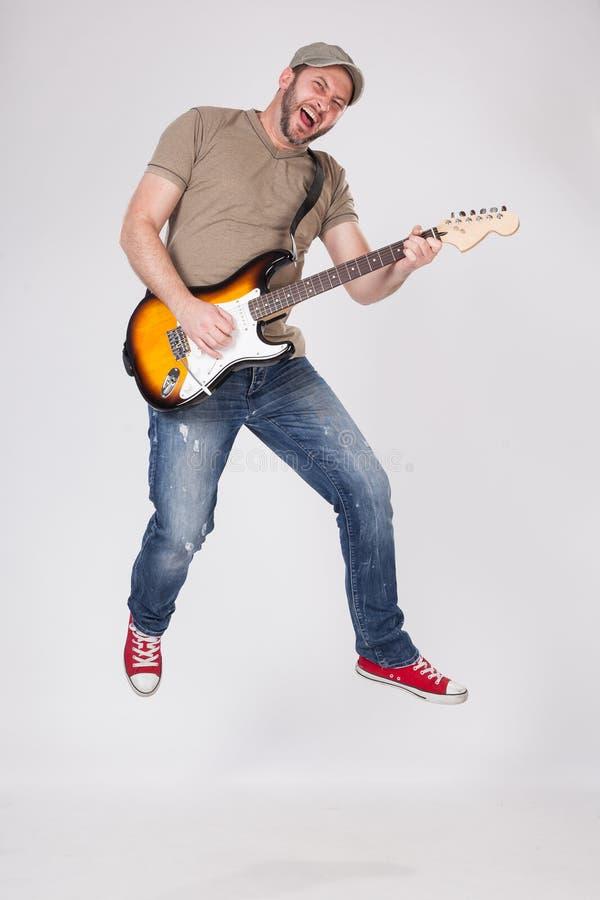 供以人员在电吉他的戏剧和跳跃在天空中 免版税库存图片