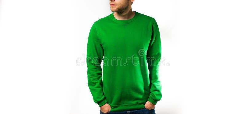供以人员在空白的绿色有冠乌鸦的立场,运动衫,在白色背景,嘲笑,自由空间 免版税库存照片
