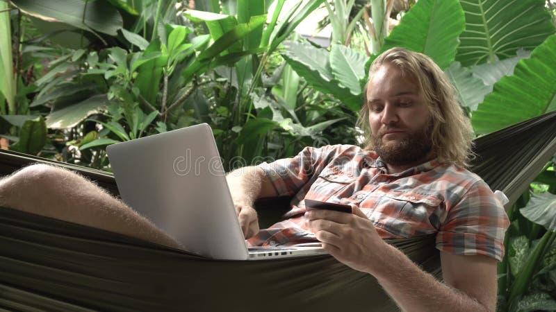 供以人员在网上购物与信用卡和膝上型计算机,当坐吊床时 库存照片