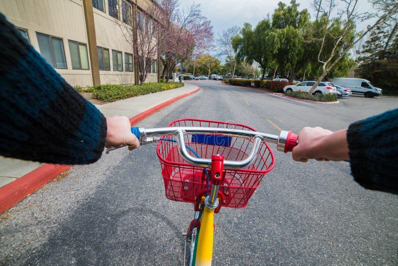 供以人员在自行车ob柏油路的骑马对工作晴天 免版税库存图片
