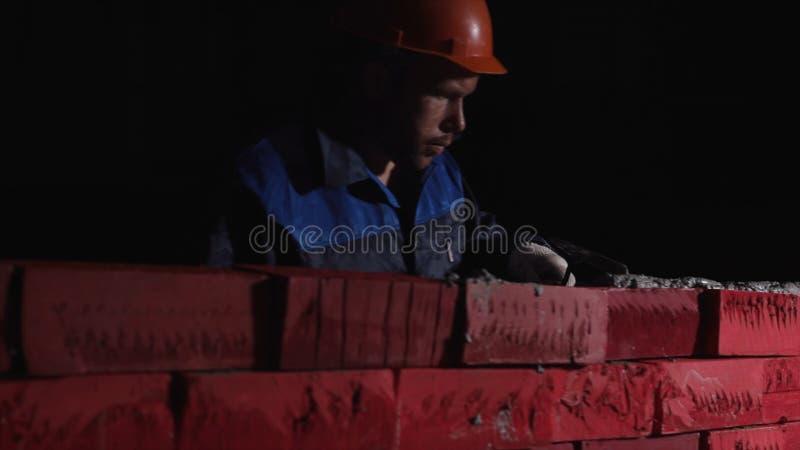 供以人员在运作的设备修造砖墙壁  股票 自我发展的概念 建立事业,到他自己, 免版税库存照片