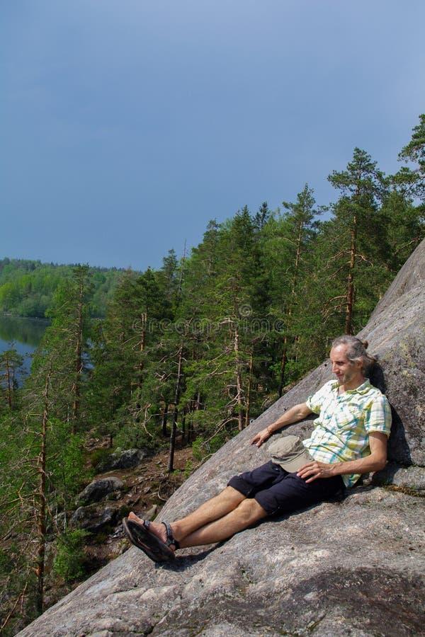 供以人员坐放松,在湖Yastrebinoye上的峭壁, Priozersky区,列宁格勒地区,俄罗斯 图库摄影