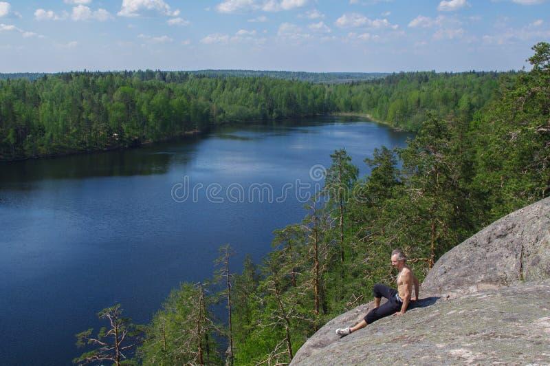 供以人员坐放松,在湖Yastrebinoye上的峭壁, Priozersky区,列宁格勒地区,俄罗斯 免版税库存图片