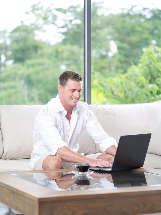 供以人员坐有膝上型计算机的沙发在避暑别墅环境里 免版税库存照片