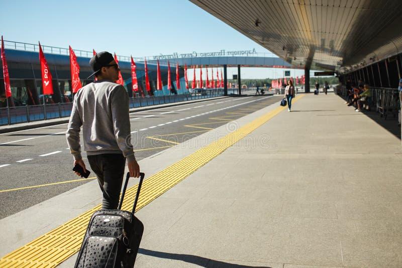 供以人员带着退出从机场终端的手提箱的旅客 免版税库存图片