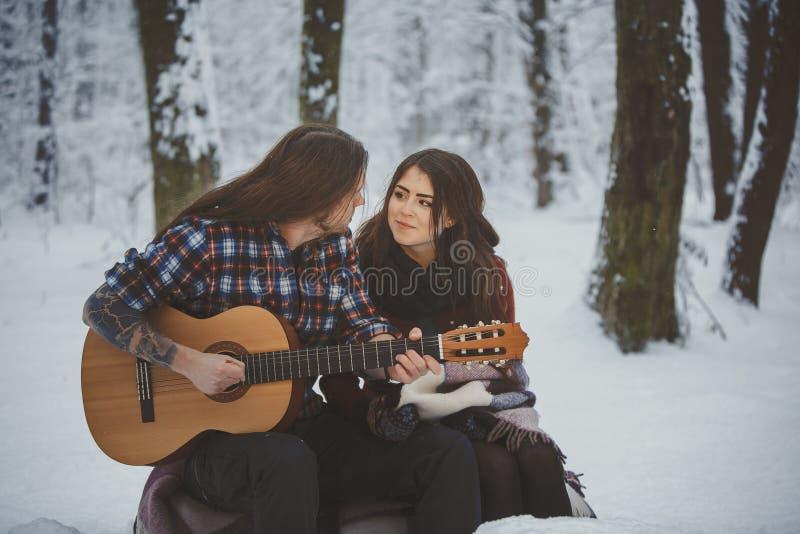 供以人员戏剧吉他给他的女朋友在冬天森林里 免版税库存图片