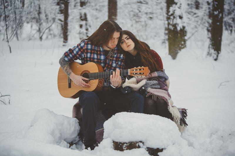 供以人员戏剧吉他给他的女朋友在冬天森林里 免版税库存照片