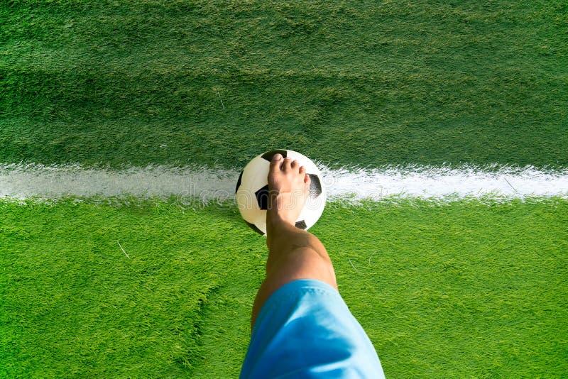 供以人员打与赤脚的足球或橄榄球球 免版税库存图片