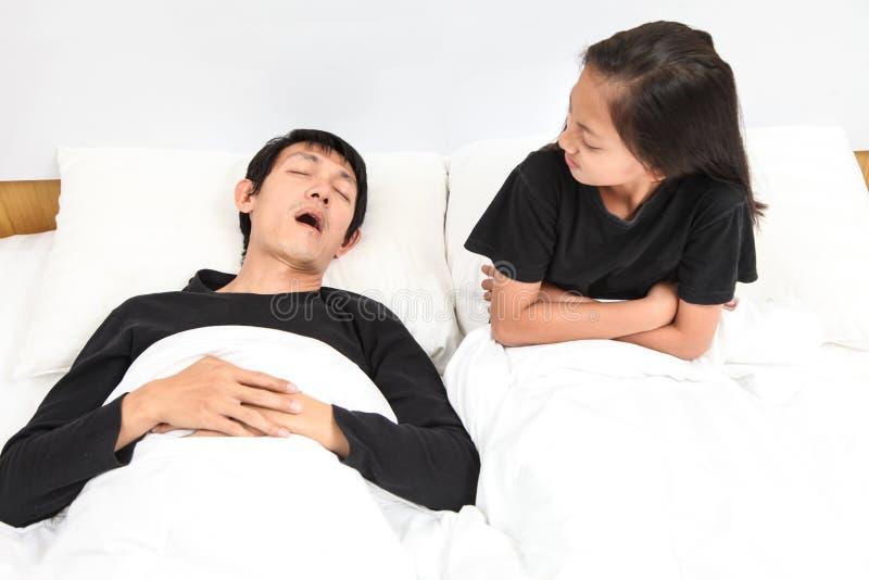 供以人员打鼾在床上,当他的盖她的耳朵的小女孩与时 免版税库存图片