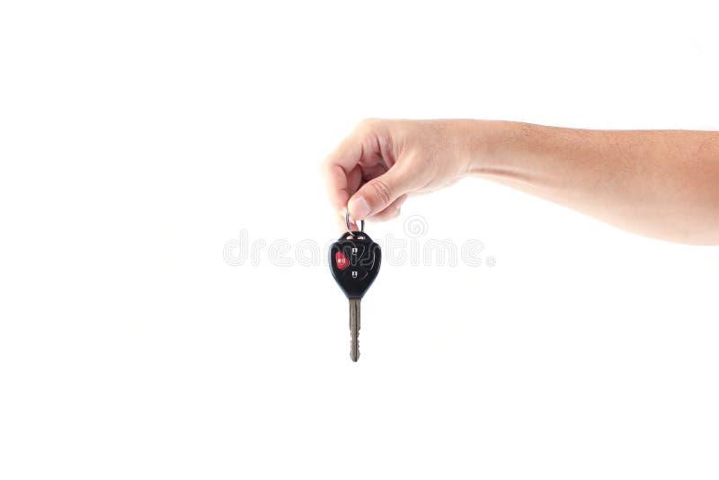供以人员把握汽车关键的手被隔绝在白色背景 免版税库存图片
