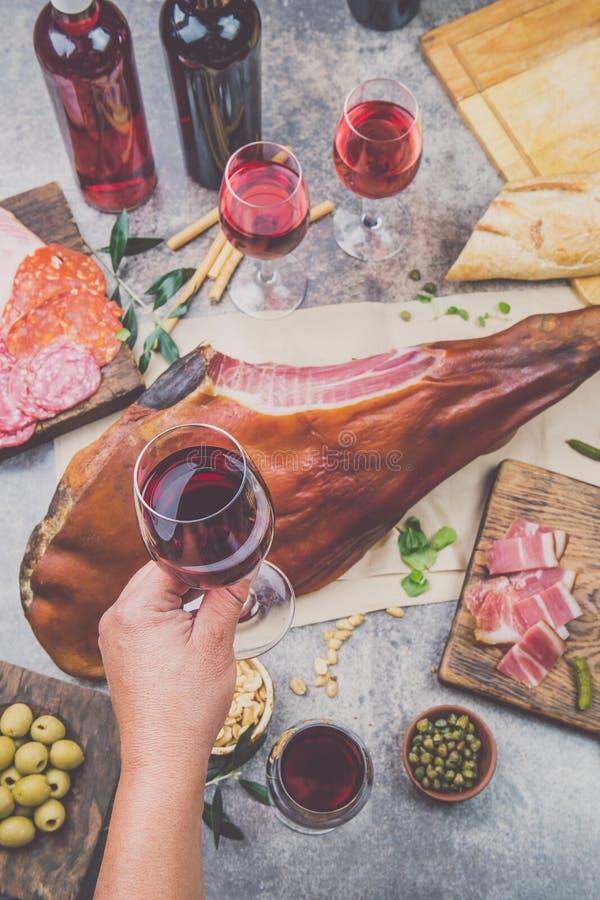 供以人员拿着与spanit的手酒杯frome上面桌或意大利开胃菜、火腿serrano的整个腿和的红色 免版税库存图片