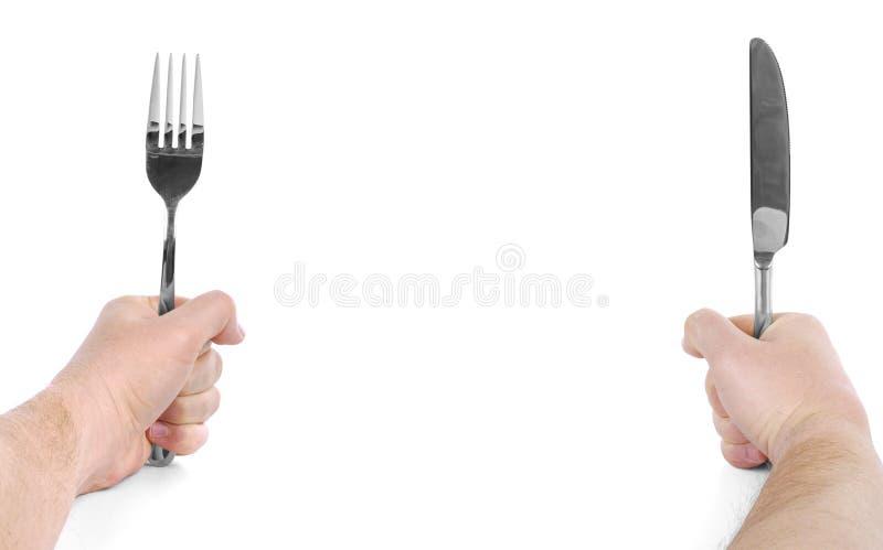 供以人员拿着叉子和刀子的手被隔绝 库存图片