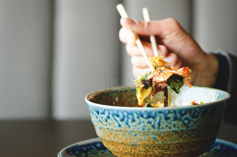 供以人员拿着在日本,泰国,中国膳食-米,蘑菇,菜板材的` s手筷子  咖啡馆 库存照片