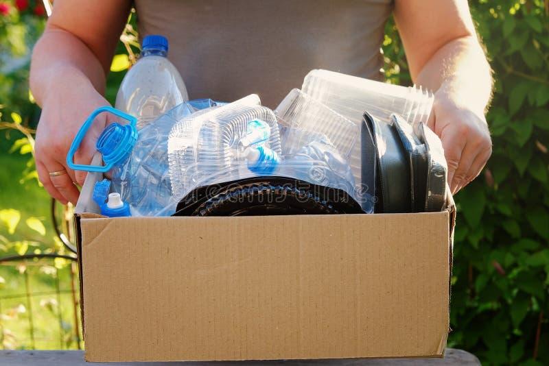供以人员拿着有塑料垃圾的` s手一个纸盒回收的 瓶概念塑料回收绳索附加的麻线水 库存照片
