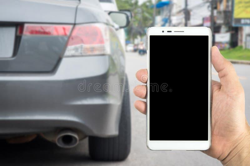 供以人员拿着有迷离汽车停放的手巧妙的电话 库存照片