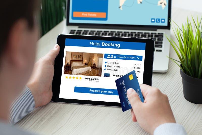 供以人员拿着有app旅馆预定屏幕信用卡的片剂 库存图片