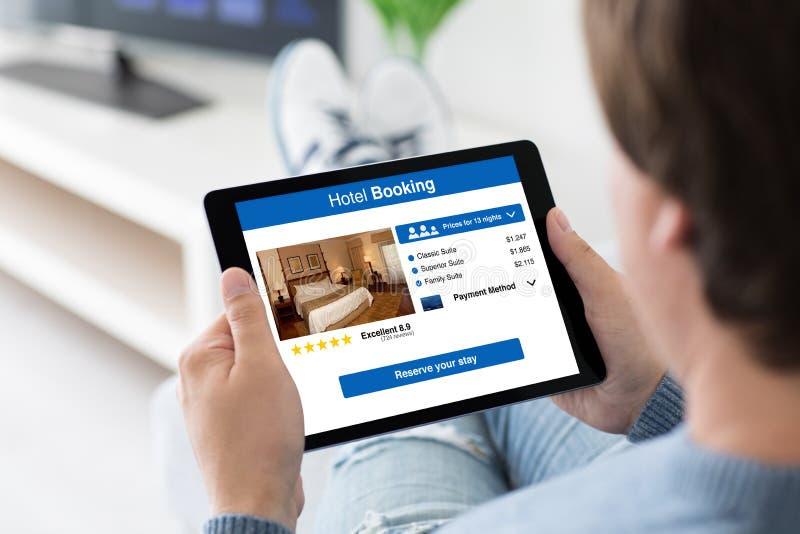 供以人员拿着有app旅馆预定的计算机片剂在屏幕上 库存照片